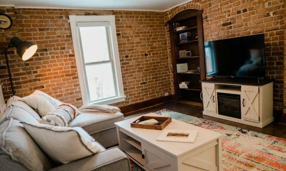 A comfortable living room with all exposed brick walls