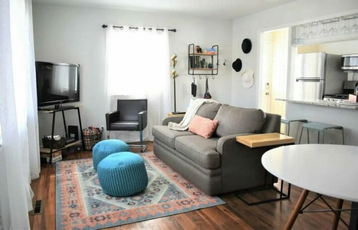 A cozy living area with a love seat, chair, ottomans and a TV; kitchen entrance in the background