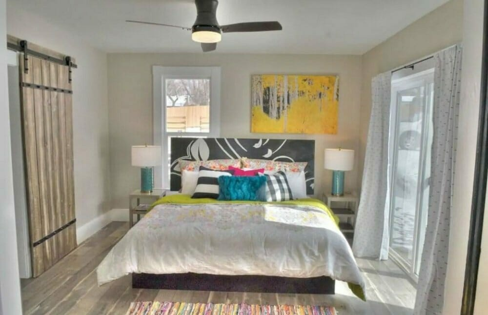 A colorful bed is nicely made, bedside tables/lamps and art hung above the bed