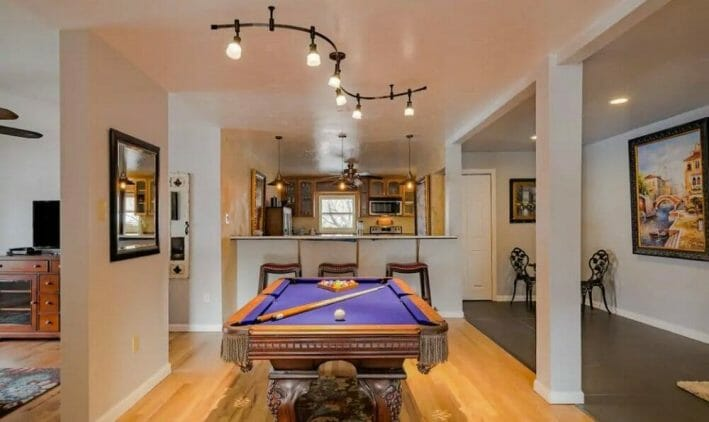 A billiards room with a large wooden pool table with bright purple felt