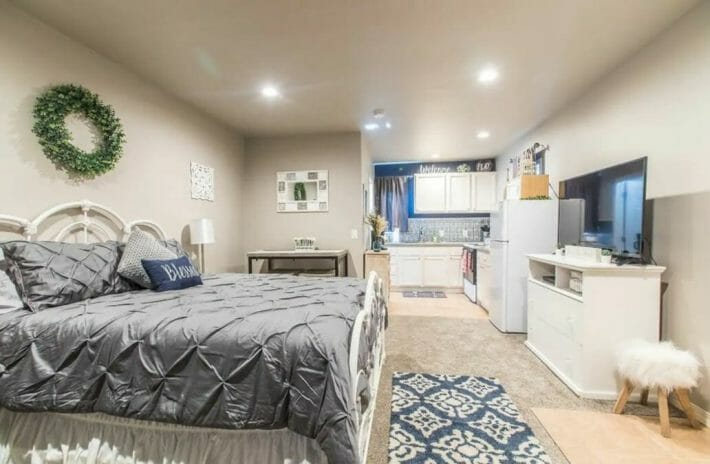 gray toned studio room with bed, tv, and full kitchen