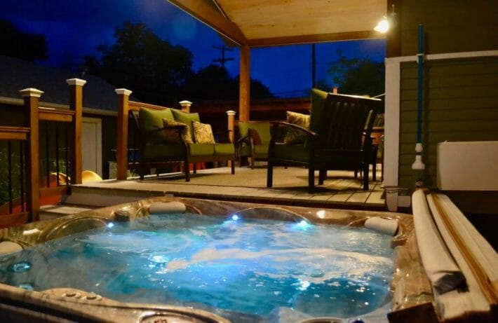 blue hued hot tub looking on to patio seating