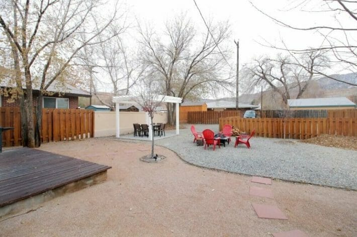 large backyard area with white pergola, two seating areas and fire pit