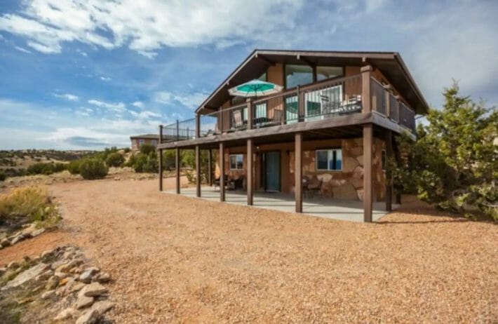 brown two-level home with large deck and gravel driveway