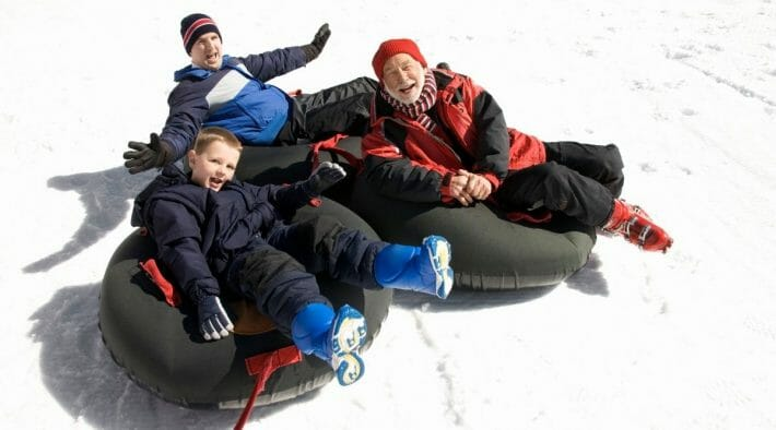 Grandfather, father and son sled close together on three sledding tubes