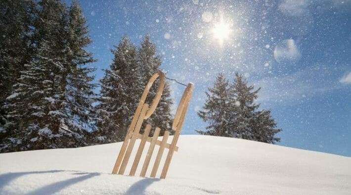 A vintage style wooden sled sticks out of snow; trees, blue skies and a bright sun in the background
