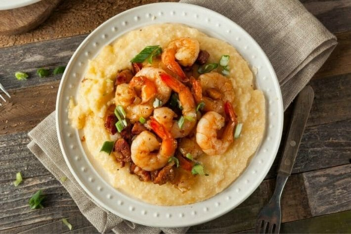 a white bowl is filled with creamy grits and topped with shrimp and bacon