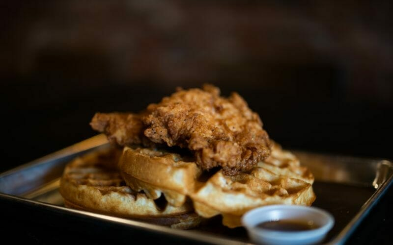 a small metal tray topped with fried chicken and waffles
