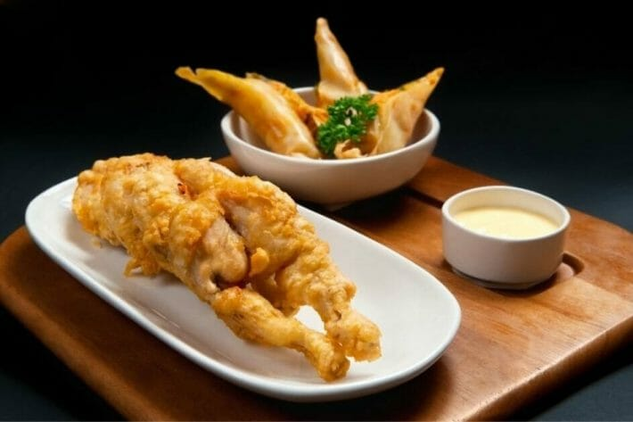 Fried frog legs line a small white plate