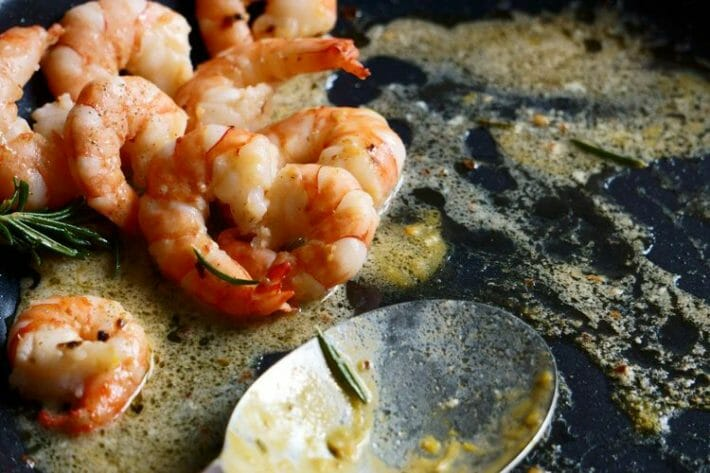 garlic butter shrimp in a partially empty dish