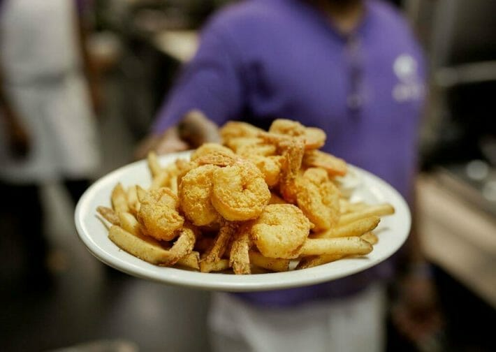 A man holds out a white plate piled high with fried shrimp and french fries