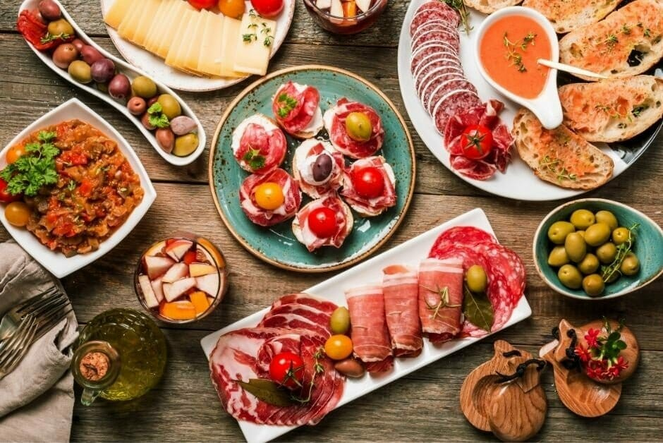 large board of various colorful tapas dishes