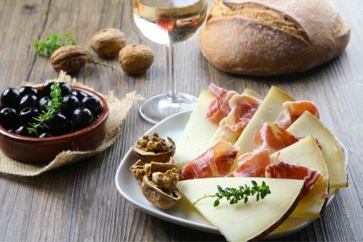 wooden table with bread, olives, cheese and white wine