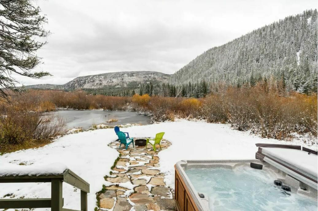Fire pit seating with a small frozen pond just beyond; snowy trees and covered ground