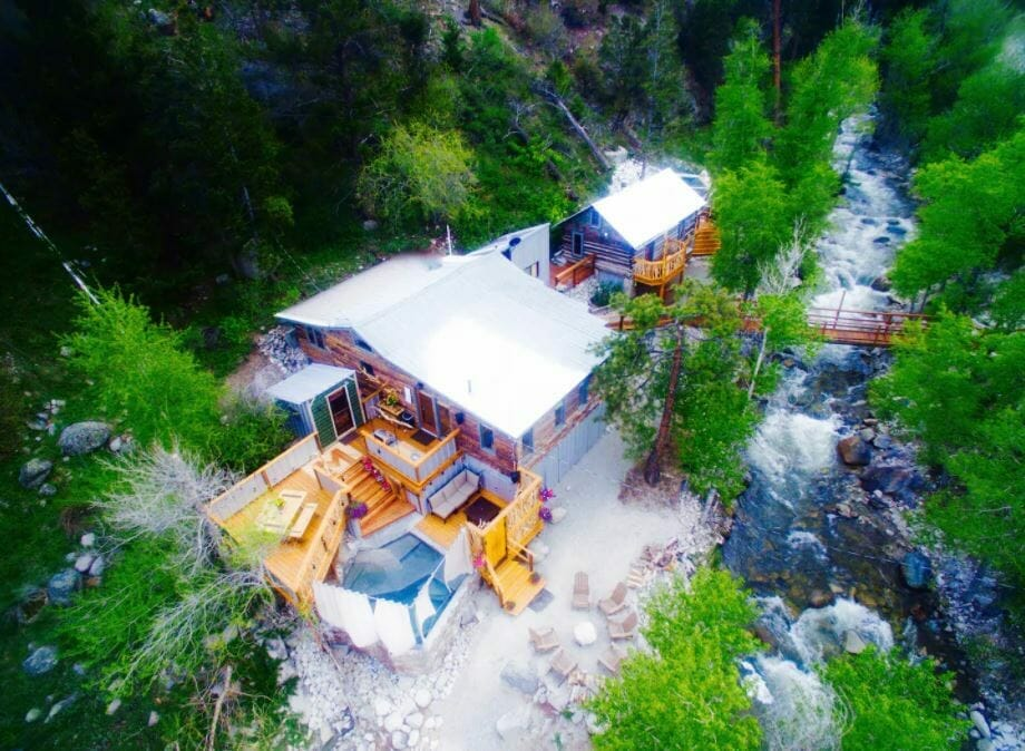 Aerial view of riverside cabin surrounded by green trees