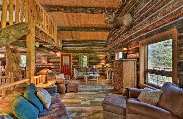 Log cabin living room with wood accents and large stuffed deer head hung