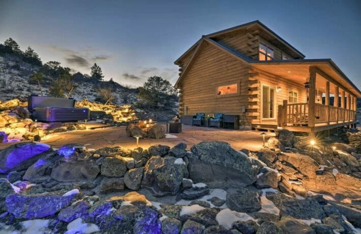 Dusk exterior view of Del Norte Colorado cabin with a hot tub in the background