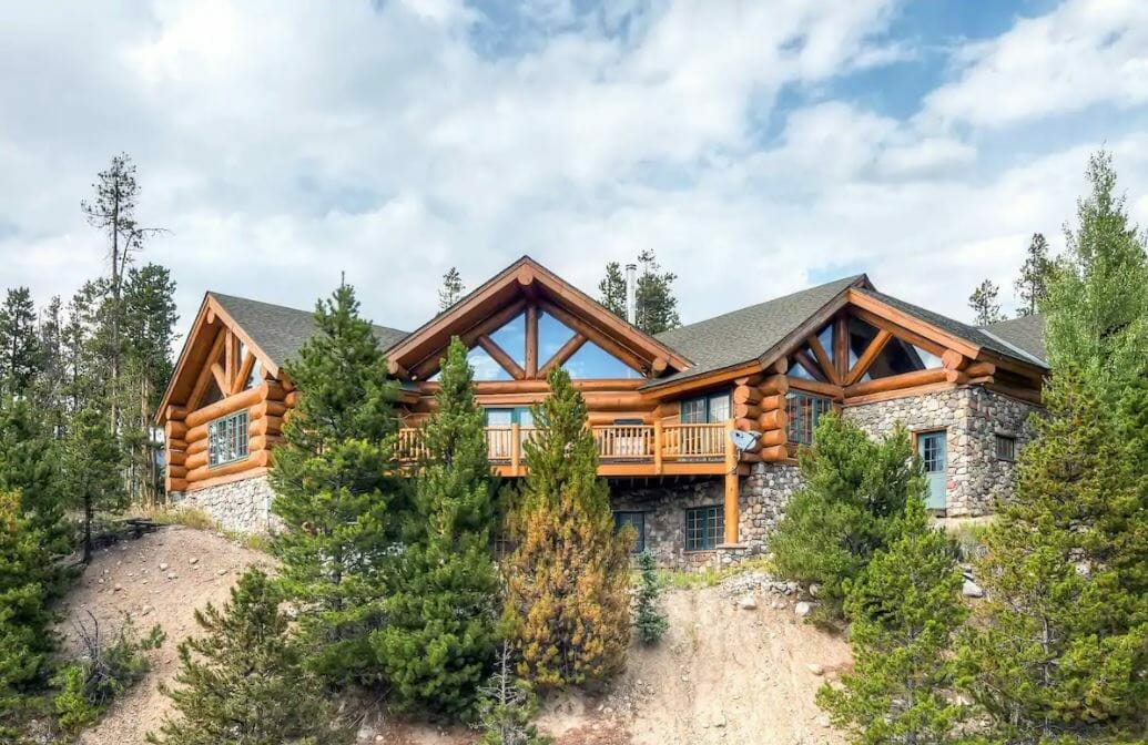 A large log cabin with large windows and stone accents in Dillon Colorado
