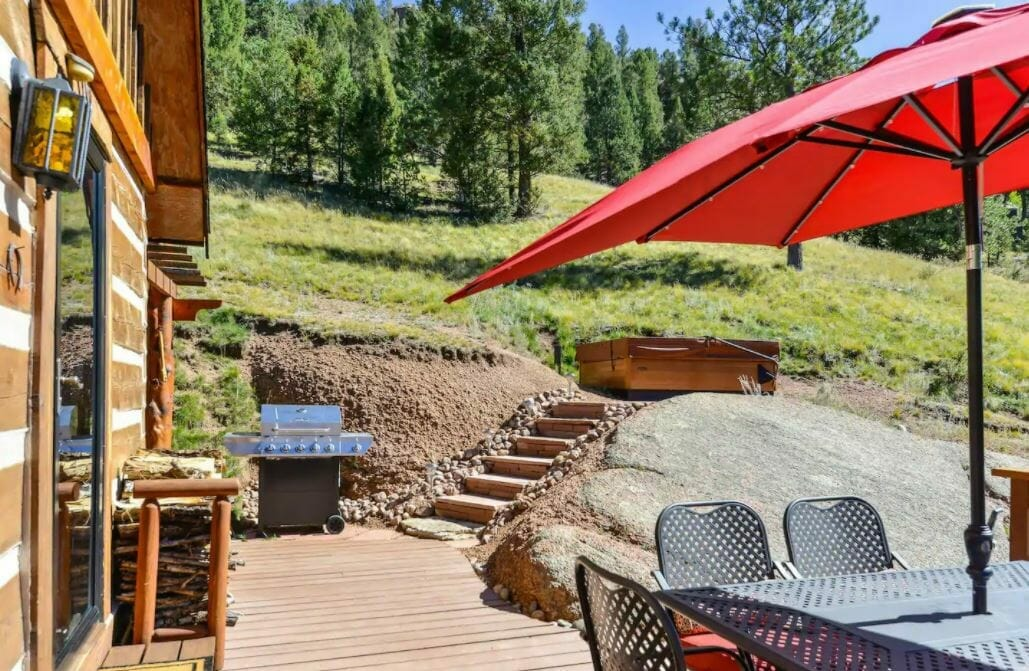 Back patio of Florrisant Colorado cabin with a hot tub in the background