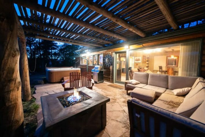 Back patio/seating area of Golden Colorado cabin with a hot tub in the background