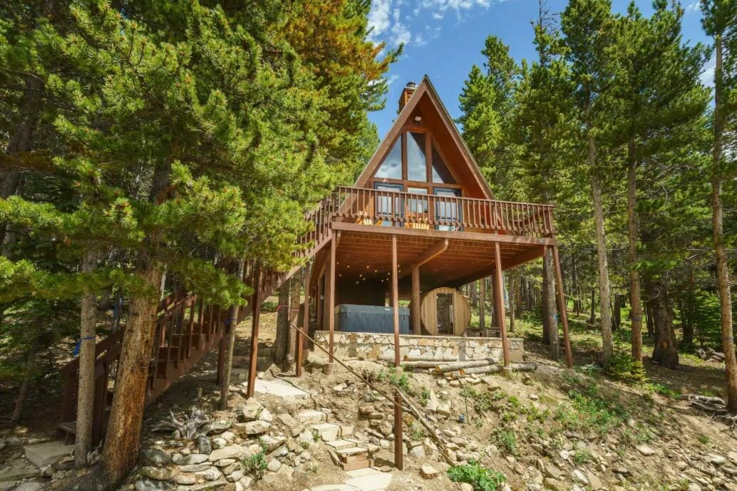 Back exterior view of an A-frame cabin amongst green pine trees