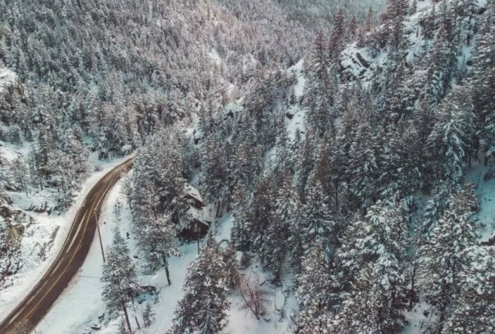 Aerial view of a snowy cabin surrounded by snow covered trees; plowed road passes on the left