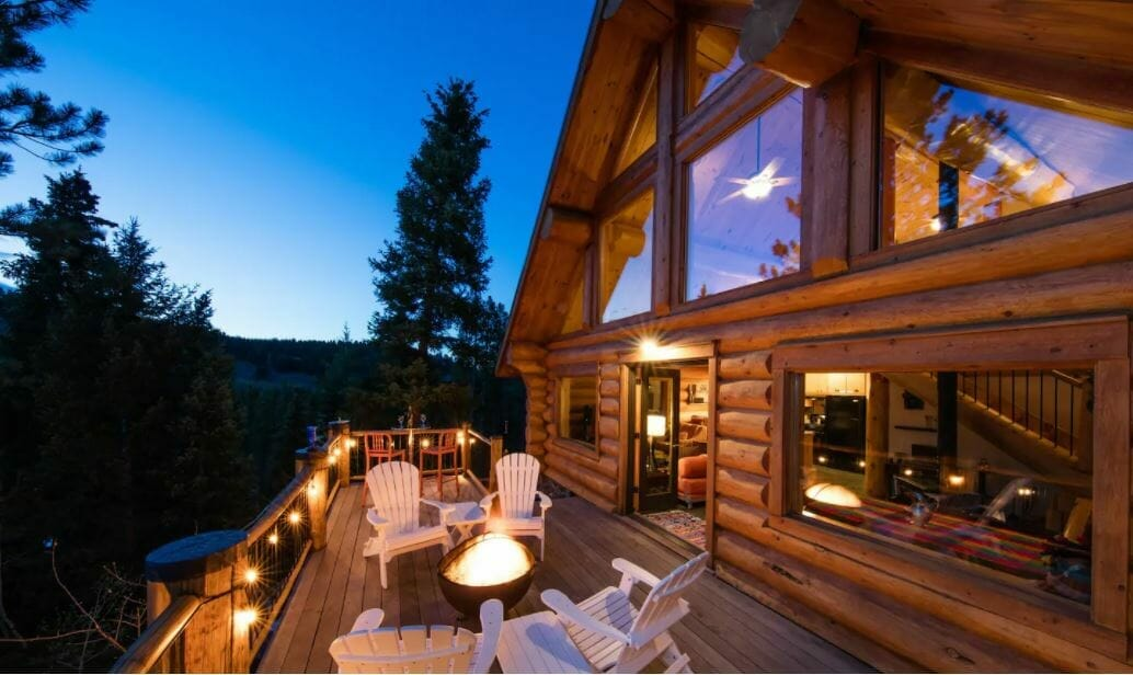 Exterior deck / seating area of large cabin at dusk; twinkly lights and a fire provide lighting