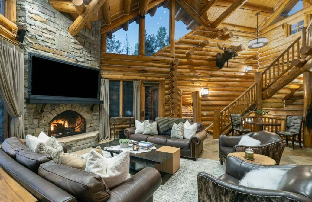 Log cabin living room with leather furniture and large stone fireplace