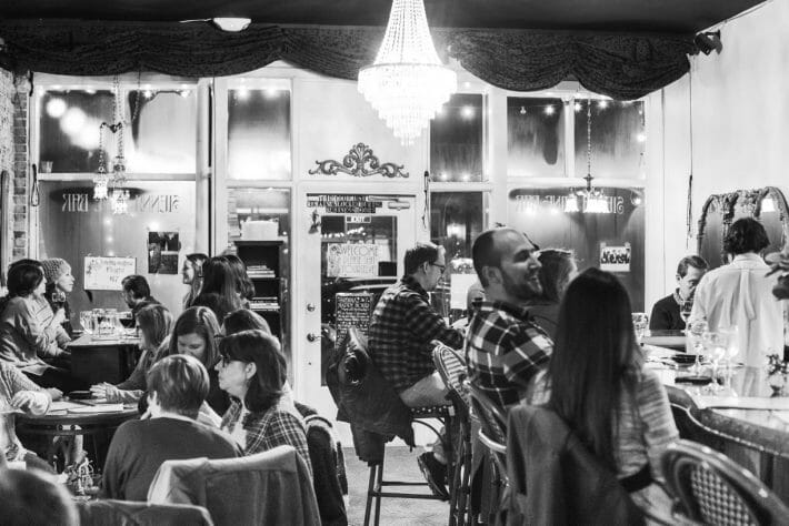 black and white interior of Sienna Wine Bar & Small Plates; patrons enjoying their evening