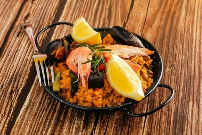 small plate of seafood paella with shrimp and lemon wedges