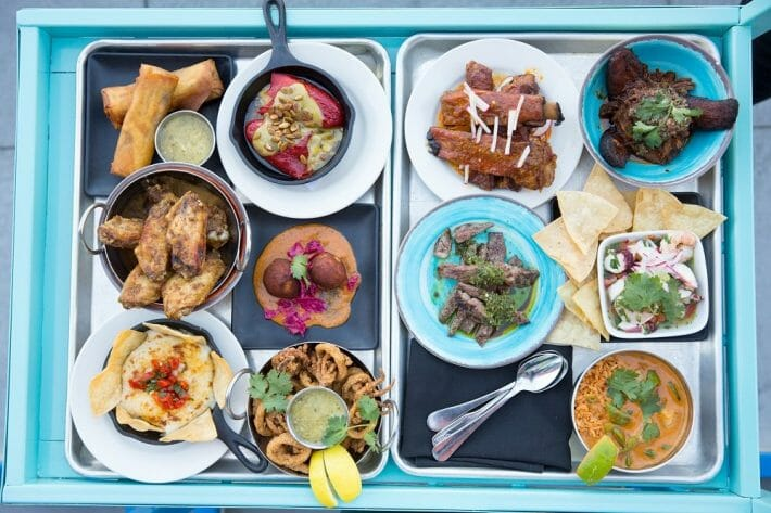 Bright blue cart is topped with many tapas dishes and small plates from Super Mega Bien in Denver