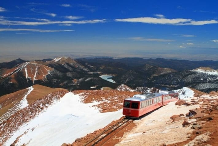 The red Pikes Peak Cogway train moves along the tracks with snowy mountains all around