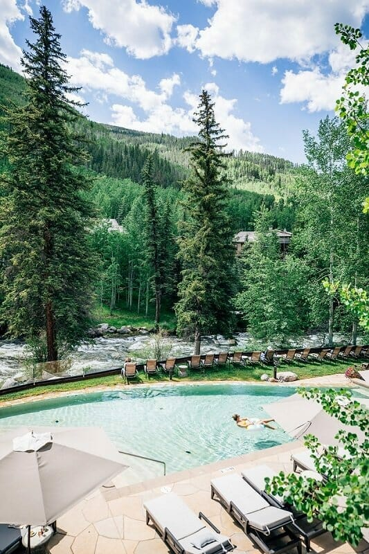 romantic getaways in Colorado are best at the pictured Grand Hyatt Vail pool overlooking a river and lots of green trees