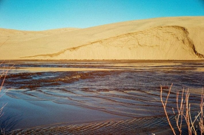 Water in the foreground with the Great Sand Dunes of Colorado in the background