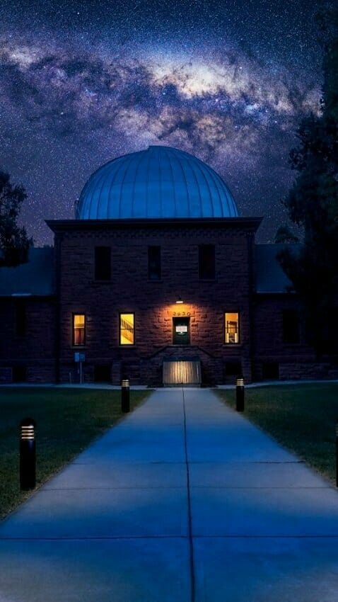 The bright milky way in the sky beyond the large domed building of the Chamberlin Observatory for stargazing in Denver