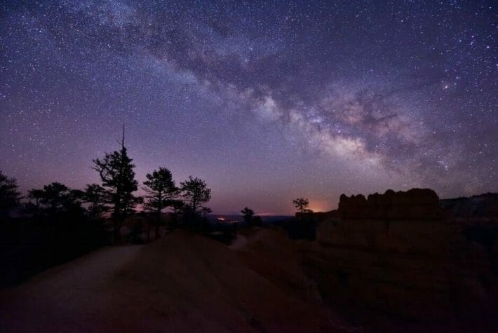 Darkened trees and rock formations underneath a purple-blue sky filled with stars